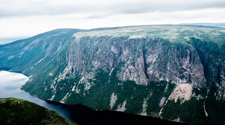 morne: Large steep cliffs partly covered in vegetation descending from plateau into inland fjord under overcast sky, at top of Gros Morne Mountain, Gros Morne National Park, Newfoundland, Canada.