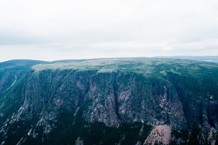 morne: Large steep cliffs partly covered in vegetation descending from plateau under overcast sky and fog, at top of Gros Morne Mountain, Gros Morne National Park, Newfoundland, Canada. Stock Photo