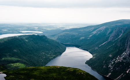 morne: Inland fjord flowing between large steep cliffs, with green landscape disappearing into clouds and fog, at top of Gros Morne Mountain, Gros Morne National Park, Newfoundland, Canada.