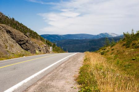 road shoulder: Empty paved asphalt road and gravel shoulder against hills and mountains in distance, in Gros Morne National Park, Newfoundland, Canada.