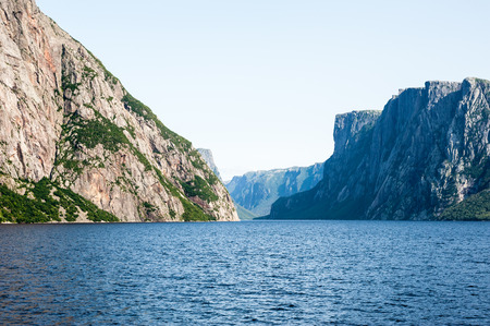 steep cliffs: Inland fjord between large rugged steep cliffs with some green vegetation on rock face, at Western Brook Pond, Gros Morne National Park, Newfoundland, Canada. Stock Photo