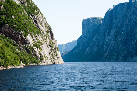 steep cliffs: Inland fjord between large steep cliffs with some green vegetation on rock face, at Western Brook Pond, Gros Morne National Park, Newfoundland, Canada.