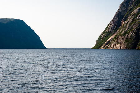 steep cliffs: Opening from inland fjord between steep cliffs against white sky, at Western Brook Pond, Gros Morne National Park, Newfoundland, Canada. Stock Photo