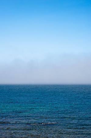 evaporate: Fog low over shallow wavy water under blue sky.