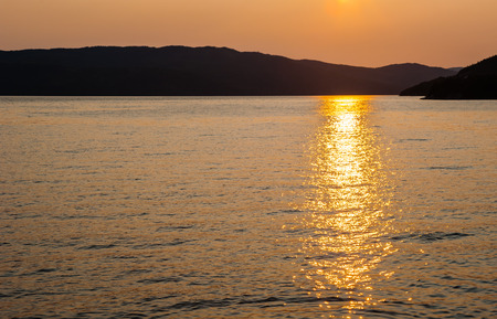 reflecting: Silhouette of hilly coast against rippled water and orange sky with setting sunlight reflecting in bay.