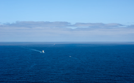three layer: Expansive deep blue ocean seascape with three boats in distance, under layer of clouds forming against light blue sky on horizon. Stock Photo