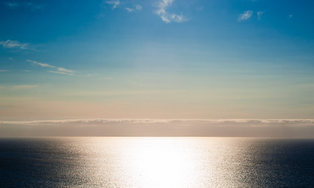 expansive: Expansive empty ocean seascape brightly illuminated by sunshine, with layer of clouds on horizon, under colorful sky turning from beige to blue. Stock Photo