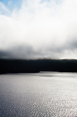 Foggy clouds low over dark coast line and wavy water illuminated by sunlight, in Newfoundland, Canada. Stock Photo