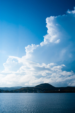 billowing: Large billowing clouds on blue sky above village on hilly coastline, near Trinity, Newfoundland, Canada.