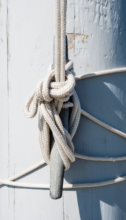 cleat: Rope looped several times around vertical cleat and tied off, casting shadow on painted white wooden mast. Stock Photo