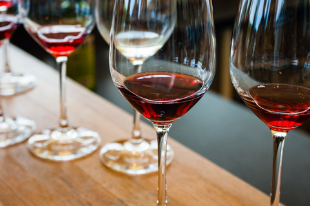 Detail of wine glasses with red wine samples, on wood counter with other glasses in background.