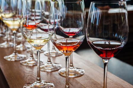 Trois verres de vin avec du blanc, rose, et des échantillons de vin rouge, sur le comptoir en bois avec d'autres verres en arrière-plan.