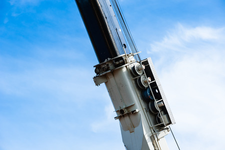 pulley: Heavy industrial pulley and cable assembly on portion of large blue and white crane arm against partly cloudy sky. Stock Photo