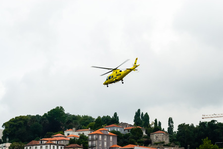 above 18: PORTO, PORTUGAL - JUNE 18, 2014: An INEM air ambulance helicopter takes off above the Douro river in overcast conditions. INEM is Portugals national medical emergency institute.