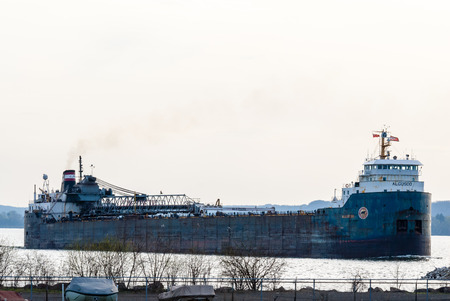 freighter: HAMILTON, CANADA - MAY 11, 2014: The self unloading Great Lakes bulk freighter Algosoo leaves Hamilton Harbour at the western end of Lake Ontario.