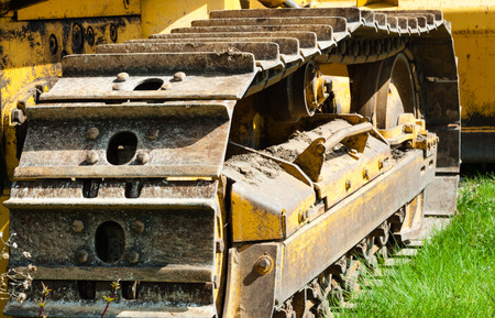 treads: Detail of muddy caterpillar tracks and treads on bulldozer parked on green grass.