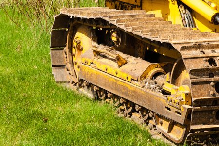 treads: Muddy caterpillar tracks and treads on bulldozer parked on green grass.