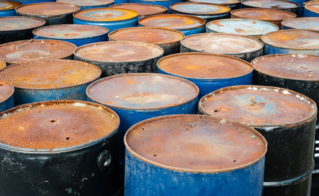 hazardous waste: Tops of many rusted blue and black storage drums. Stock Photo
