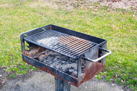 Dirty rusted barbecue grill with old cinders and ashes, near grass in park.
