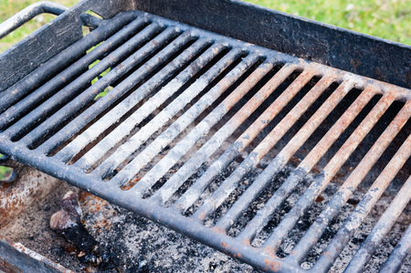 Detail of dirty rusted barbecue grill with old cinders and ashes. Stock Photo