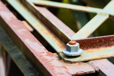 metal fastener: Detail of hexagonal metal screw fastener on corner of partly rusted steel bars and plates.