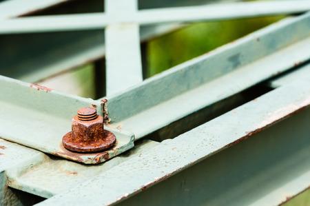 metal fastener: Detail of rusted hexagonal metal screw fastener on corner of painted steel bars and plates.
