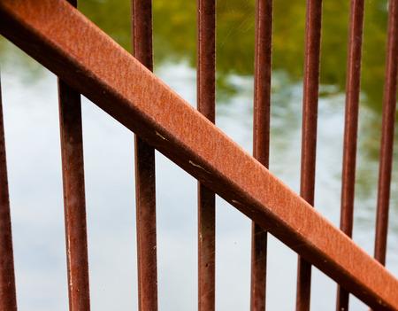 diagonally: Large rusted metal beam diagonally across smaller vertical metal bars.