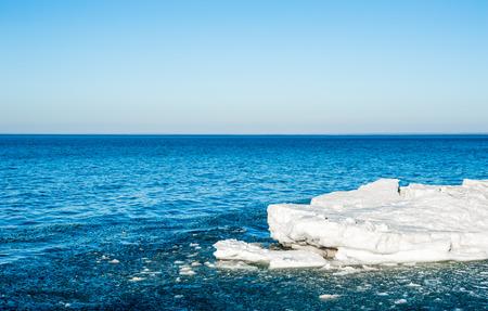 Fonte de morceaux de glace flottant dans l'eau bleue sous un ciel vide, sur la baie Georgienne, Ontario, Canada. Banque d'images - 86684527