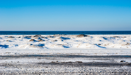 Frozen ice and sand dunes on beach in winter by empty lake horizon under clear blue sky, near Georgian Bay, Ontario, Canada.