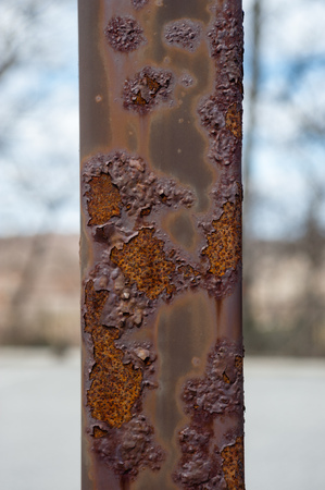 corrosion: Detail of rusted metal post with paint blistering and peeling off. Stock Photo