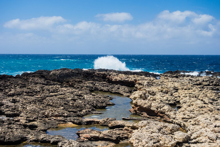 Rocky coastline and tide pools with splashing waves under partly cloudy sky in Malta.