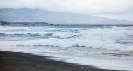 Powerful ocean waves crashing on wet beach under cloudy sky with island in background, in Azores, Portugal.
