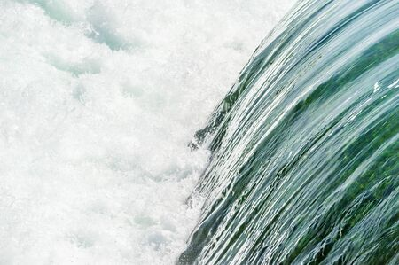 Smooth green water flowing into white churning rapids on Niagara River, Ontario, Canada.