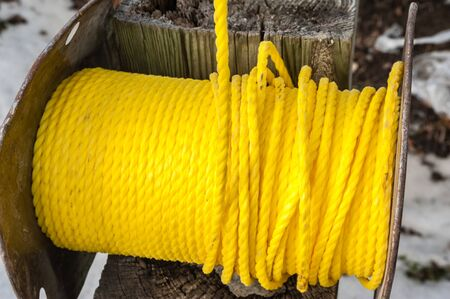 Spool of wound plastic yellow rope on wooden post.