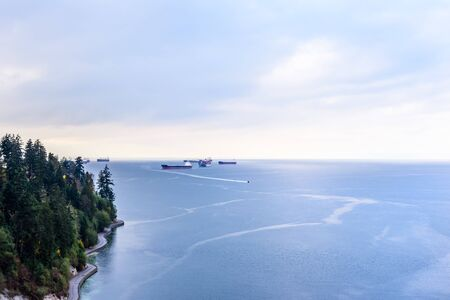 Cargo ships anchored in bay with boat leaving near shore of Stanley Park in Vancouver, British Columbia, Canada.
