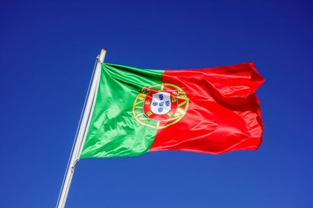 Flag of Portugal flapping in wind against empty blue sky.