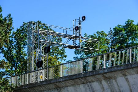 Railway signals and signs on metal frame among trees above bridge with fence.