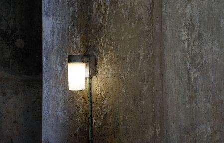 Single lamp shining on dark dirty concrete wall. 写真素材