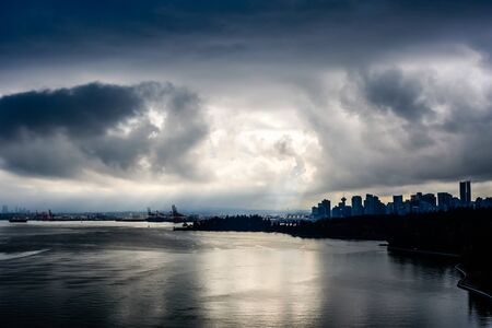 Sun breaking through dark clouds in dramatic high contrast over Vancouver, British Columbia, Canada. 写真素材