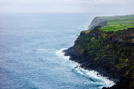 Ocean at high cliffs with lush farms on plateau, in Azores, Portugal.