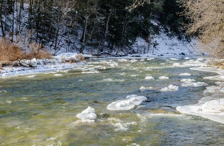 River flowing in winter with chunks of ice and snow.