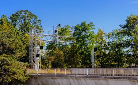 Railway signals and signs on metal frame above bridge with fence among trees. 写真素材