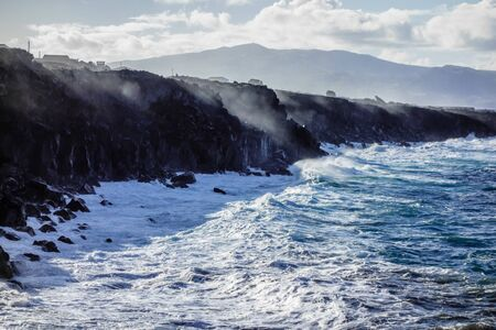Ocean waves splashing on jagged cliffs with spray reflecting sunlight, in Azores, Portugal.