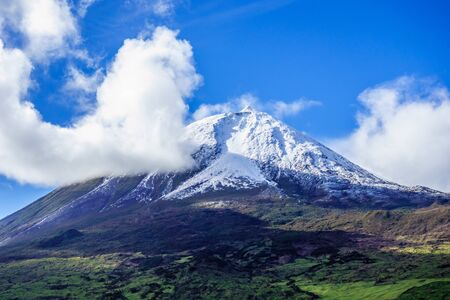Mount Pico volcano summit covered in snow under blue sky and clouds, in Azores, Portugal.