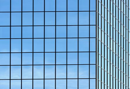 Corner of office building windows in square grid pattern reflecting sky.