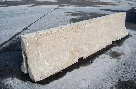 Concrete barrier on dirty empty asphalt.
