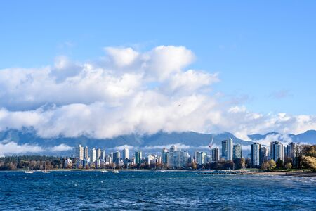 Skyline of condominiums in the West End of Vancouver, British Columbia, Canada, viewed from across bay with fog and clouds lifting.