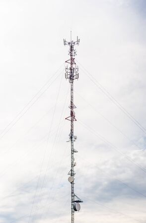 Tall red and white metal communications antenna tower with dishes and supporting cables, against cloudy gray sky. 写真素材