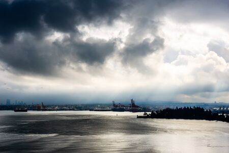 Sun breaking through from behind dark clouds in high contrast over water in Vancouver, British Columbia, Canada. 写真素材