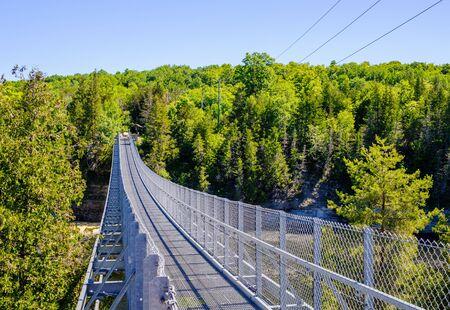 Metal pedestrian suspension bridge over Ranney Gorge in Campbellford, Ontario, Canada. Фото со стока